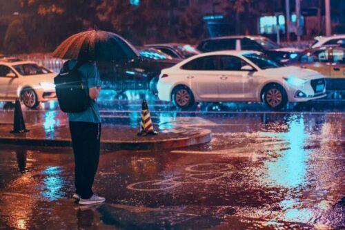 雨の中信号待ちをしている人と車の風景写真