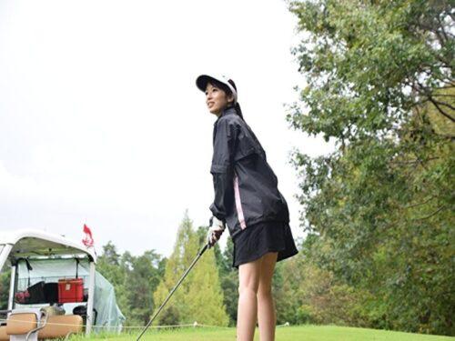 雨ゴルフでティーショットを打つゴルフ女子