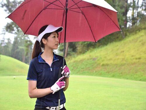 雨ゴルフで他のプレイヤーを見つめるゴルフ女子