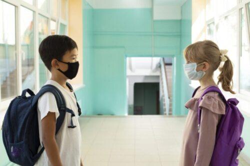 マスクをして廊下に立つ小学生